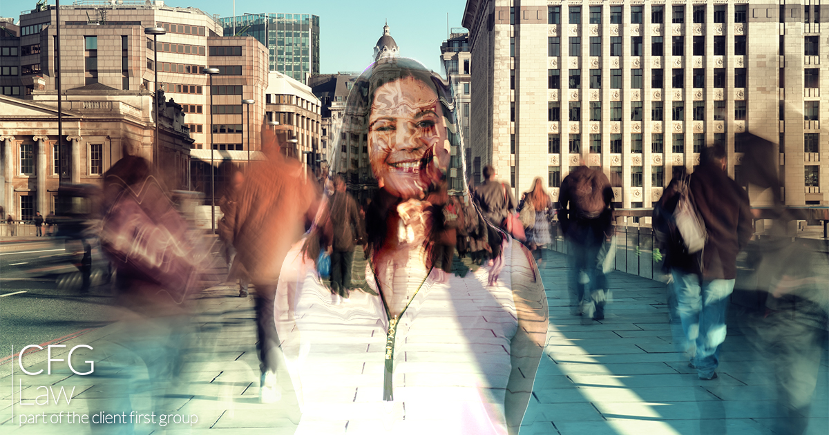 A smiling woman is transparent allowing view of passing foot traffic through her